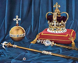 Colour photograph taken in 1952 of the regalia in front of a blue drape. St Edward's Crown rests on a red cushion that has gold trimming.