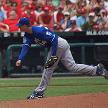 A man in a blue baseball jersey and gray pants stands having pitched a baseball with his right hand.