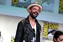 A brunette man wearing a fedora, white t-shirt, and black jacket laughs as he looks off to the crowd