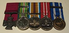 A row of five medals with the Victoria Cross on the left; the other four medals are circular with multicoloured ribbons.