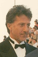 Profile of a man seen with a crowd of people in the background. He is wearing a tuxedo complete with a black suit, white collared shirt, and black bowtie.