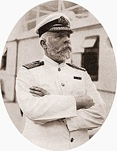 Photograph of a bearded man wearing a  white captain's uniform, standing on a ship with his arms crossed.