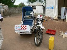 An off-road motorcycle fitted with knobbly mud tyres and a single sidecar, which has a cover over the passenger seat and a UNICEF logo on the front