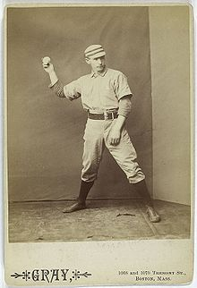 A sepia-toned baseball card image of a man in old-style white baseball pants, jersey, and cap pantomiming throwing a baseball with his right hand