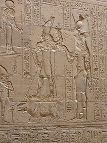 Relief of a falcon-headed man standing on a hippopotamus and driving a spear into its head as a woman stands behind them