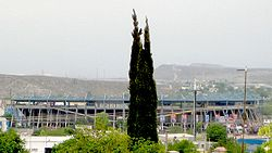 photo of stadium from outside with mountains in distance and trees in foreground