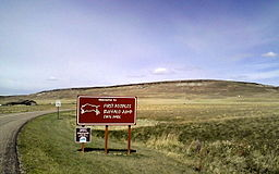 "A sign saying ""Welcome to First Peoples Buffalo Jump State Park"" in script type with a drawing of a buffalo next to it in white on a brown background. Behind it are some buildings and a large rise in the earth."