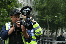 Two uniformed FIT police officers standing on the street, one has a camera with a large lens and then other has a small camcorder