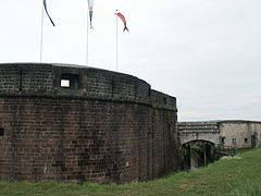 photographie de la Tour des Bourgeois surmontée de trois drapeaux