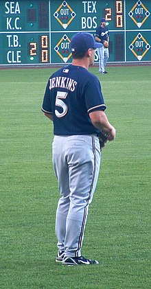 A man in a navy-blue baseball jersey and cap and gray baseball pants stands on a baseball field.
