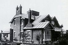 Black and white photograph of the facade of the brick house. Two storeys with a two-pronged chimney rising up the front wall.