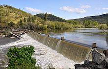 Un grande fiume scorre su una diga e in una piscina ribollente sotto.  Verdi colline fiancheggiano la riva opposta.