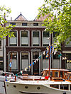 foto van Pand met lijstgevel ter breedte van vijf vensterassen met stucversieringen en vensters met afgeronde hoeken.