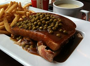 "Chicken sandwich - A Quebec-style ""hot chicken"", topped with green peas"