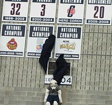 Connecticut Huskies mascot Jonathan pulling down two black curtains, unveiling placards honoring the 2002–03 and 2003–04 women's basketball national championship teams