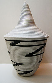 Photograph depicting a bowl shaped off-white woven basket with tall conical lid and black zigzag pattern