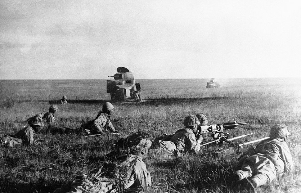 Japanese soldiers creeping in front of wrecked Soviet tanks