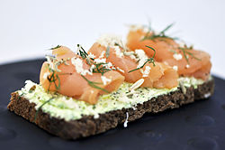 Gravlax on rye bread , garnished with pepper , lemon and dill