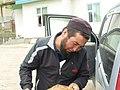 Kyrgyz man pouring gasoline to his car Nura village.jpg