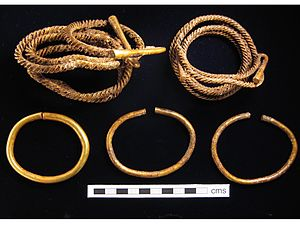Torc - Two uncleaned Bronze Age twisted bar torcs with flared cylinder terminals, as often found folded up, with bracelets, England