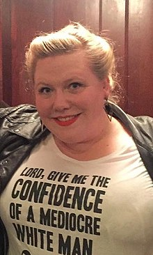 "Lindy West wears a black jacket and white t-shirt printed with the words ""Lord, give me the confidence of a mediocre white man."""