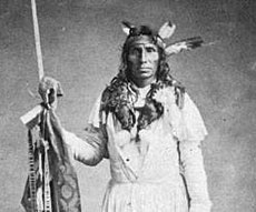 Little Crow in three quarter height view wearing a headress with three feathers and carrying a spear