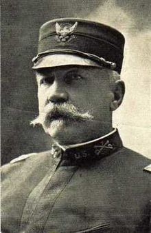 Black and white picture of Louis Carpenter, a white male with a large mustache wearing his US Army uniform. His Army uniform has a high collar with an emblem of crossed swords and the letters U.S. next to it. He is wearing a round hat with an emblem of an eagle clutching something.