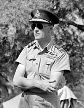 Outdoor half portrait of man in light-coloured military uniform with peaked cap, wearing sunglasses
