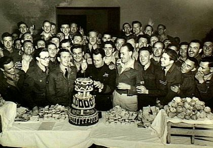 Large group of cheering men in military uniforms surround a man cutting a three-decker birthday cake on a long table