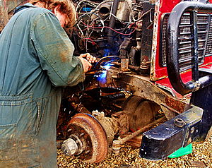 Seorang pria pengelasan MIG patch ke depan chassis Land Rover.