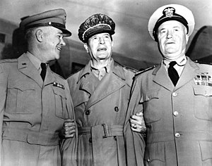 Three men in neat uniforms smiling. MacArthur is wearing his distinctive cap and no tie.