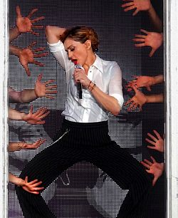 A middle-aged blond woman wearing a white shirt and black pants sings to a microphone, while to her sides several human hands can be seen.