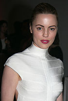 A photo of Melissa George, with her hair tied back, smiling, and wearing a white dress.