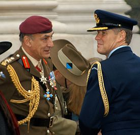 Two men in military uniforms—one blue and one green—standing in front of a stone monument