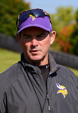 Color full-length photograph of Zimmer, gesturing with his hands, walking on a football field, wearing a grey pullover, grey shorts and purple baseball cap with the Minnesota Vikings logo.