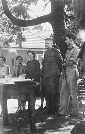 Black and white photograph of a group of three women and two men wearing military uniform. All members of the group are standing under a tree and are looking at a table.