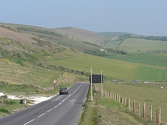 A3055 road - Military Road near Compton Farm (ahead). Automatically in the event of a landslide, or manually in very poor weather, the sign (to the right here) can be illuminated to close the road at this vulnerable point.