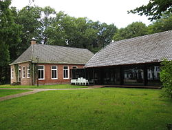 A red brick building and a glass building, both having grey tile roofs, with green grass in the front and green trees in the background