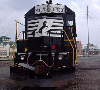 Dover, Delaware - A Norfolk Southern GP38-2 parked on the team track in Dover with the old railroad depot in background.