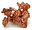 Um cristal de um mineral de metal de cor de cobre de pé sobre uma superfície branca