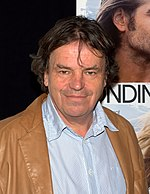 A man is standing in front of a poster. He is wearing a beige coat over an unbuttoned light blue collared shirt.