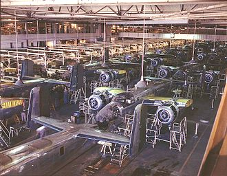 "North American Aviation - B-25 Mitchell bomber production line at the North American Aviation plant, Inglewood, California, October 1942. The plane's outer wings have yet to be added, which enables the two side-by-side assembly lines to be closer together. The outer wings will be attached outdoors, in the ""sunshine"" assembly line."