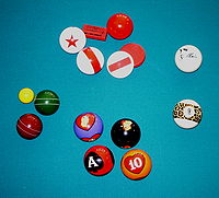 various novelty pocket billiards balls clockwise from the top red and white balls and markers from a proprietary game called starball an elvis presley