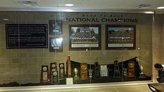Northwest Missouri State Bearcats football - National football championship trophy room at Bearcat Stadium prior to its national title in 2009. The two trophies in the middle are national championships in 1998 and 1999. The four trophies on the left are for appearances in the title games in 2005, 2006, 2007, and 2008. Northwest in 2009 made unprecedented fifth consecutive national title game in 2009 and won its third title. The stick in the middle left is the Hickory Stick in the contests with Truman State.