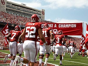 Football players run onto a football field in two rows under a crimson banner.
