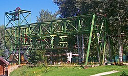 An L-shaped green open latticework steel structure on a small rise. The long end runs parallel to the ground to where it is supported by two diagonal beams in front of some deciduous trees with light trunks. On the bottom of the middle section is another section housing a large red pulley wheel parallel to the ground. A smaller red pulley and cable can be seen in the top of the short section.