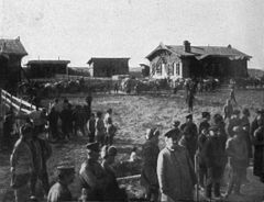 P438a Nansen station on the Amur railway. A row of telegas with labourers returning home passing the station.jpg