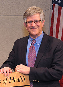 Dr. Paul Offit is a gray-haired man with brainy-specs and a suit, posing at a podium, smiling the smile of a man who's quite famous and just a bit embarassed about it.