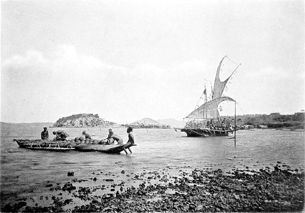 Black and white photograph of six men loading a boat on a beach, with a sailing boat just off shore.