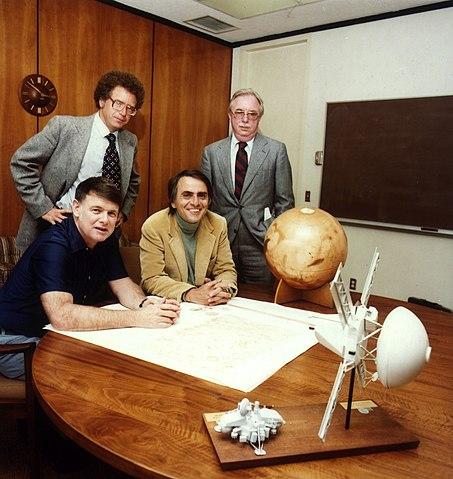 Учредители Планетарного общества на собрании, посвящённом созданию организации, 1980 год. На переднем плане модели АМС Викинг в сборе и её составной части— автоматической марсианской станции. На заднем плане глобус Марса